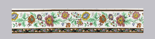 Multi-colored flowers and foliage of assorted variety. At the bottom of the border is a narrow band containing a garland hung with small scale flowers and crosses. The effect is vaguely that of Indian-chintz. Printed in greens, pinks, yellow, gold, mauve, blue, dark red, orange and black on a white background.