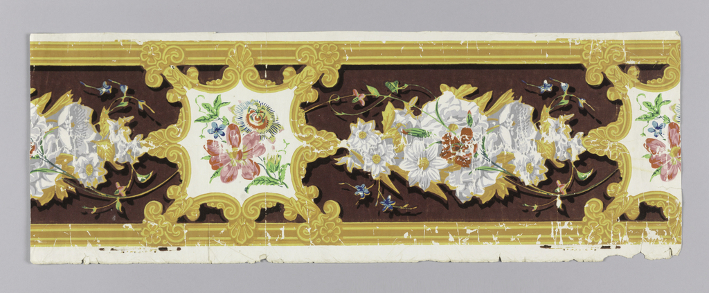 Between striped edgings, the wide central band contains flowers enframed by cartouches which are separated by garlands of flowers. Each cartouche has eight points alternating between palmettes and rosettes/acanthus leaves. The background is flocked; printed in yellow, gold, green, blue, red, pink and a purple flocked background.  H# 312 ?