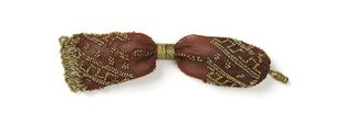 Crocheted red silk ornamented with gold beads in diagonal patterns.  Two gold metal rings at opening; a fringe of twisted gold beads at one end; a gold drop at the other.