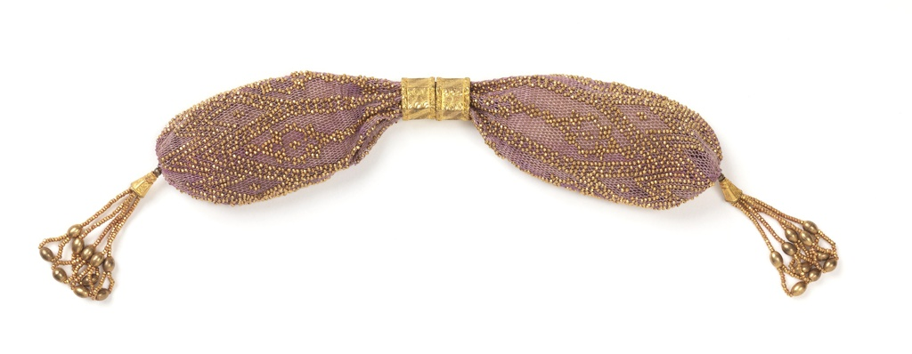 Pale violet silk purse ornamented with gold beads in zigzag and diamond pattern. Two engraved hexagonal rings control side opening; tassels at either end are of small gold beads ending in loops formed by larger gold beads.