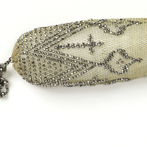 White silk netted purse ornamented with cut steel bands in pattern of triple zigzags, dots and crosses. Two faceted steel rings control side opening; tassels of cut steel beads at either end.
