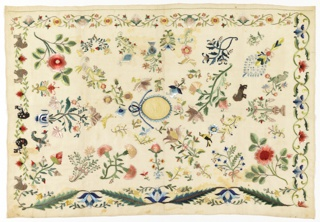 Sampler scattered with flowers and birds embroidered in many colored silks. Central medallion in gold with blue serrated edge and a bow. Several dogs, perhaps poodles, appear amongst the flowers.