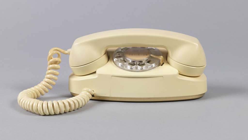 White plastic form consisting of oval body, the handset cradled horizontally across top above clear plastic rotary dial; white coiled cord on left connects handset to body.