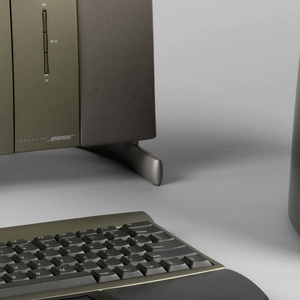 Upright, shallow rectangular metallic gray monitor unit (a); CD drawer and controls below screen flanked by long rectangular speakers; short base with curved foot. Separate gray keyboard (b) with leather wrist wrests; trackpad in front center. Separate short, tapering columnar gray CPU (c), including sound system woofer.
