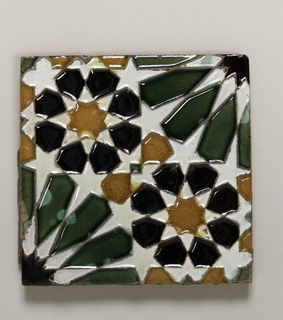 Red earthenware with white slip.  Geometric interlaced pattern, forming two diagonally placed eight-petal rosettes in black, with yellow center.  In opposite corners elongated green petals, part of larger rosette, extending over four tiles.