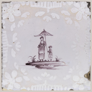 """Square tile. Grayish white ground centered with manganese figures in the Chinese style, of a woman and boy holding parasol, both figures standing on a low mound. Bordered with crude floral ornament in overglaze white. Example of """"bianco sopra bianco"""" technique."""