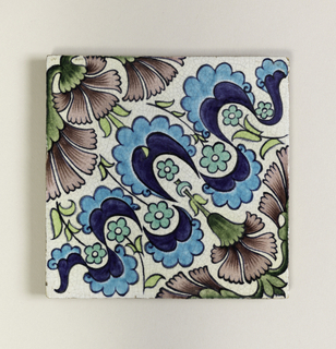 Square tile of buff clay with grog added. On white crackled glaze a diagonally placed design of scalloped blue and turquoise shapes, green flowers and purple pinks. Part of large design.