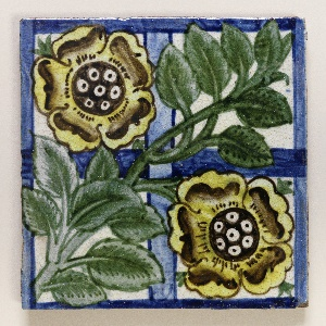 Square tile of reddish buff clay with grog added. On white crackled glaze blue border and cross bars, over which a diagonally set plant with two large yellow flowers in painted.