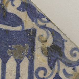 Square tile of buff clay with thin underfired opaque grayish-white glaze. Underglaze blue painting of diagonally placed heraldic shield with eagle and three pointed arches. Above, helmet with plumes, and foliated scrolls surrounding the shield.