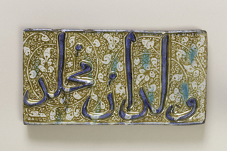 Horizontal rectangle.  Raised blue inscription on brown and white scrolled lustre-painted ground with turquoise spots.