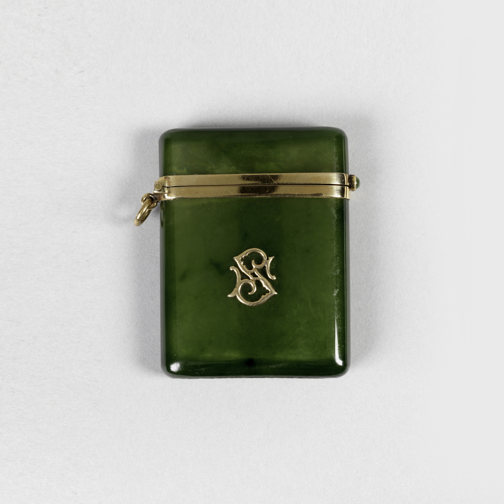 """Rectangular, slightly translucent nephrite box body and attatched lid, the bottom edge of lid has gold surround as does the upper edge of body. Lid is opened with nephrite cabochon release button. On box front is attached monogram """"S"""". Gold link attached beneath gold hinge on left side. Striker carved into bottom with hatch marks."""