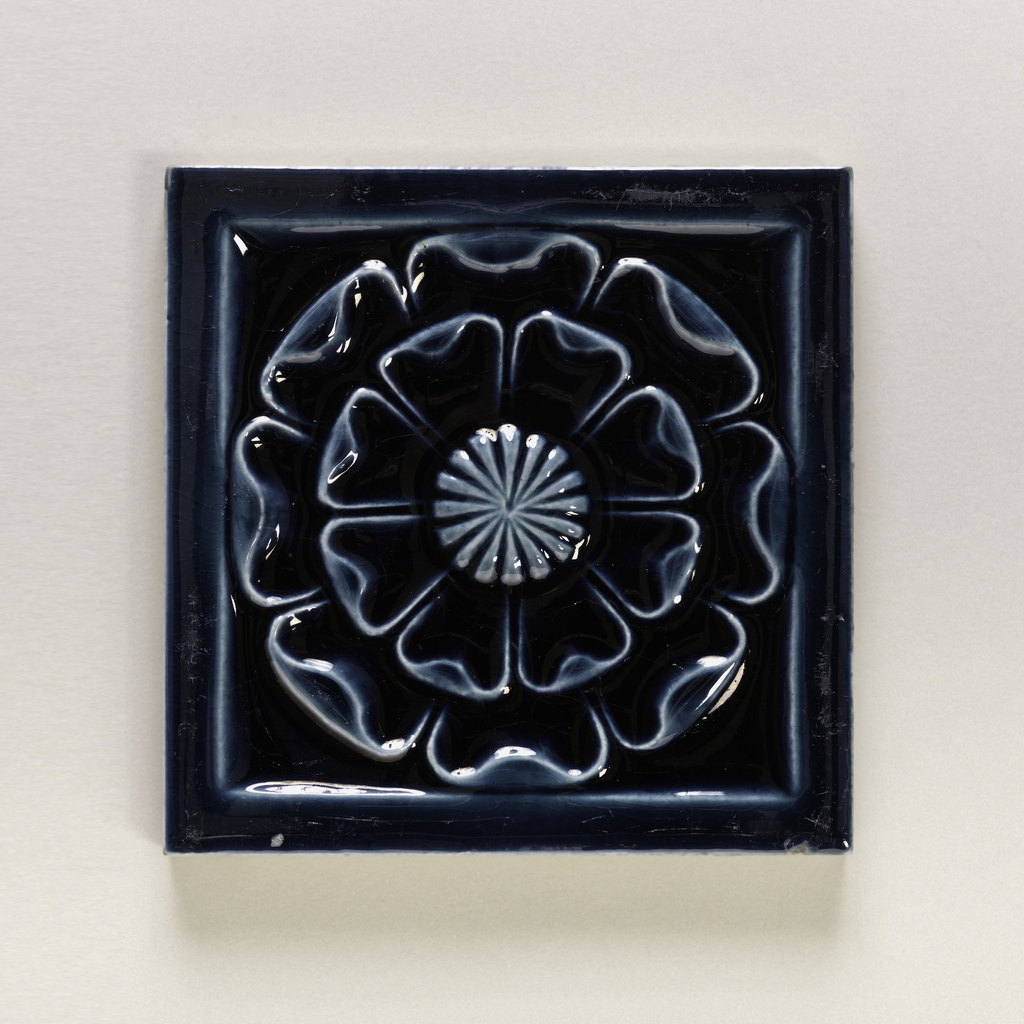 Square, molded tile made of white clay, Face of tile is decorated with stylized flower having double row of petals; framed in plain border; glazed deep blue.