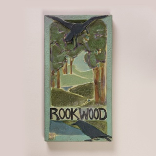 """Tile """"Rookwood"""" advertising sign with rocks, forest scene. Rookwood Faience.   Rectangular plaque made of coarse white clay, molded. Design in relief of landscape with trees and winding river, with two ravens or rooks. One bird with outstretched  wings at center top of plaque, the other perched at bottom, below Rookwood logo. In various colored mat glazes, some with cracklature: dark and light greens, brown, tan, pale sea-green, fushia and black. Border and sides in a pale sea-green. Back not glazed."""