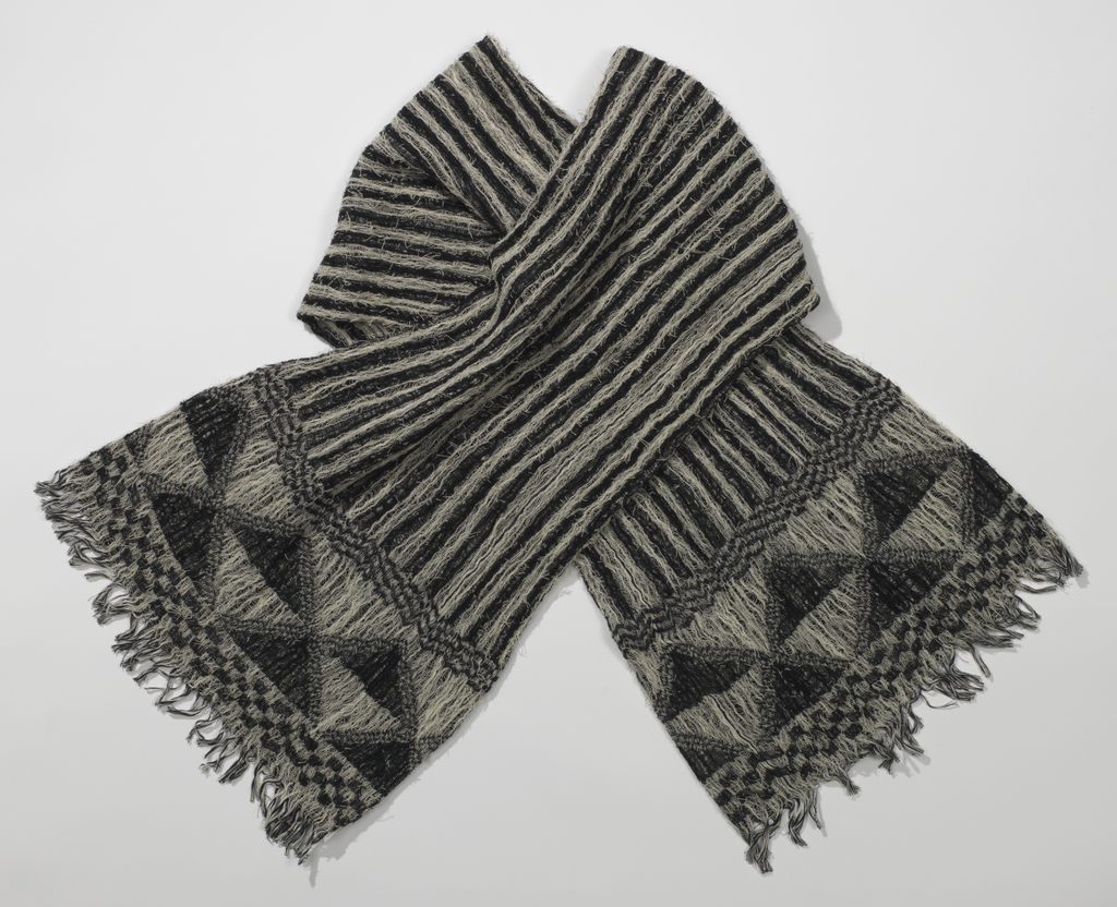 Black and white scarf with a field of vertical stripes and a border at each end with a wide band of stacked triangles and two narrow borders of off-set rows of rectangles, with a small fringe.