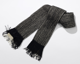 Narrow tubular scarf with fine black and white stripes and solid black ends with fringe.