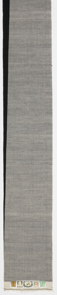 Kimono length split diagonally over its entire lenth between gray and black. The gray color is the result of crossing a white warp with a black weft; the black area is a black warp and black weft. The hand-spun silk has a more cotton-like feel than reeled silk. Original design dates from 1910.
