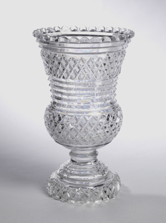 Baluster shaped, with flaring rim and scalloped lip; short knopped stem, high stepped base; cut in strawberry diamond pattern all over with prismatic rings under lip, middle of sides and top of base; glass very reflective.