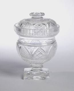 Round body with tall vertical fluted lip rim; double knopped stem, square base; domed top with flat cushion finial cut with diamonds; lower part of top and sides of body cut with arched panels filled alternately with small diamonds or strawberry diamonds, row of blazes base of body.