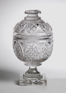 Round bowl on faceted waisted stem and thick square base; sides of bowl cut with arched panels of strawberry diamonds, fans between, each, a row of vertical fluting above to lip, domed cover with flattened conforming panels of strawberry diamonds and fluted rim.