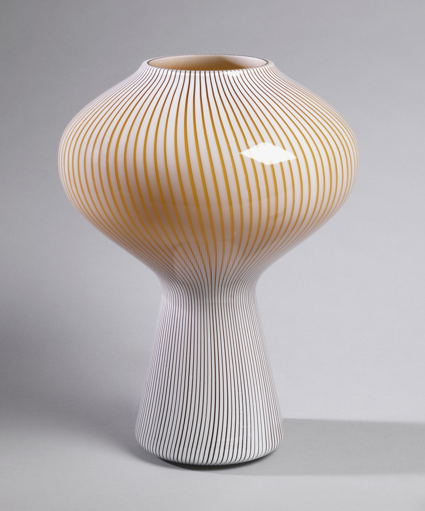 Brown-yellow glass cased with white opaque threads to create overall vertical stripes; overlaid with clear glass. Mushroom shape with tapered base, bulbous body curved inward to form circular mouth.