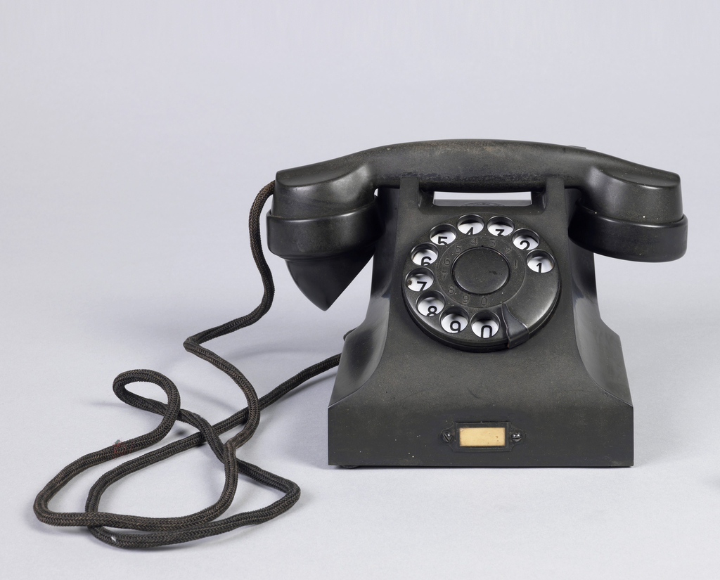 Black rotary telephone with square base; one-piece handset resting in cradle in top of body; black dial on front, with black numbers on white ring visible under finger holes.