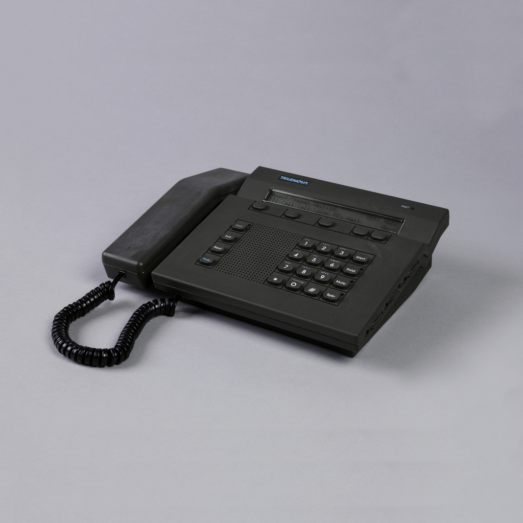 Dark grey rectangular body and handset; body with speaker, function buttons, and numeric keypad below long horizontal digital display screen. Logo at top in bright blue; long rectangular angled handset in cradle on left, black spiral cord at bottom.