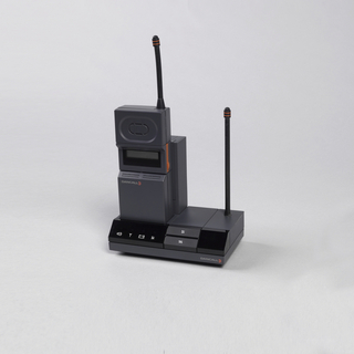 Cordless dark grey telephone consisting of rectangular base unit with slanted digital display in front and upright antenna on right, well on left for separate handset unit. Upright rectangular handset with flip-down panel in lower half, digital display in front, upright antenna top right.