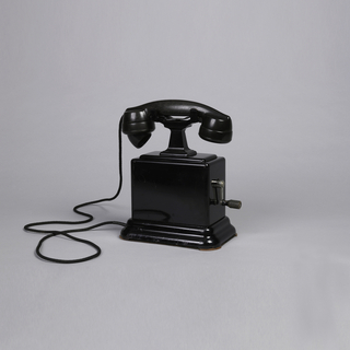 Black telephone with large block base and stepped foot, crank on one side. Handset resting on top held by stand with two prongs, straight black cord.