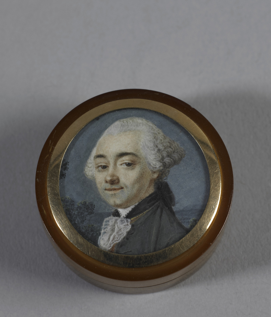 Round patch box with portrait miniature of a man with white wig; under glass, gold rim.