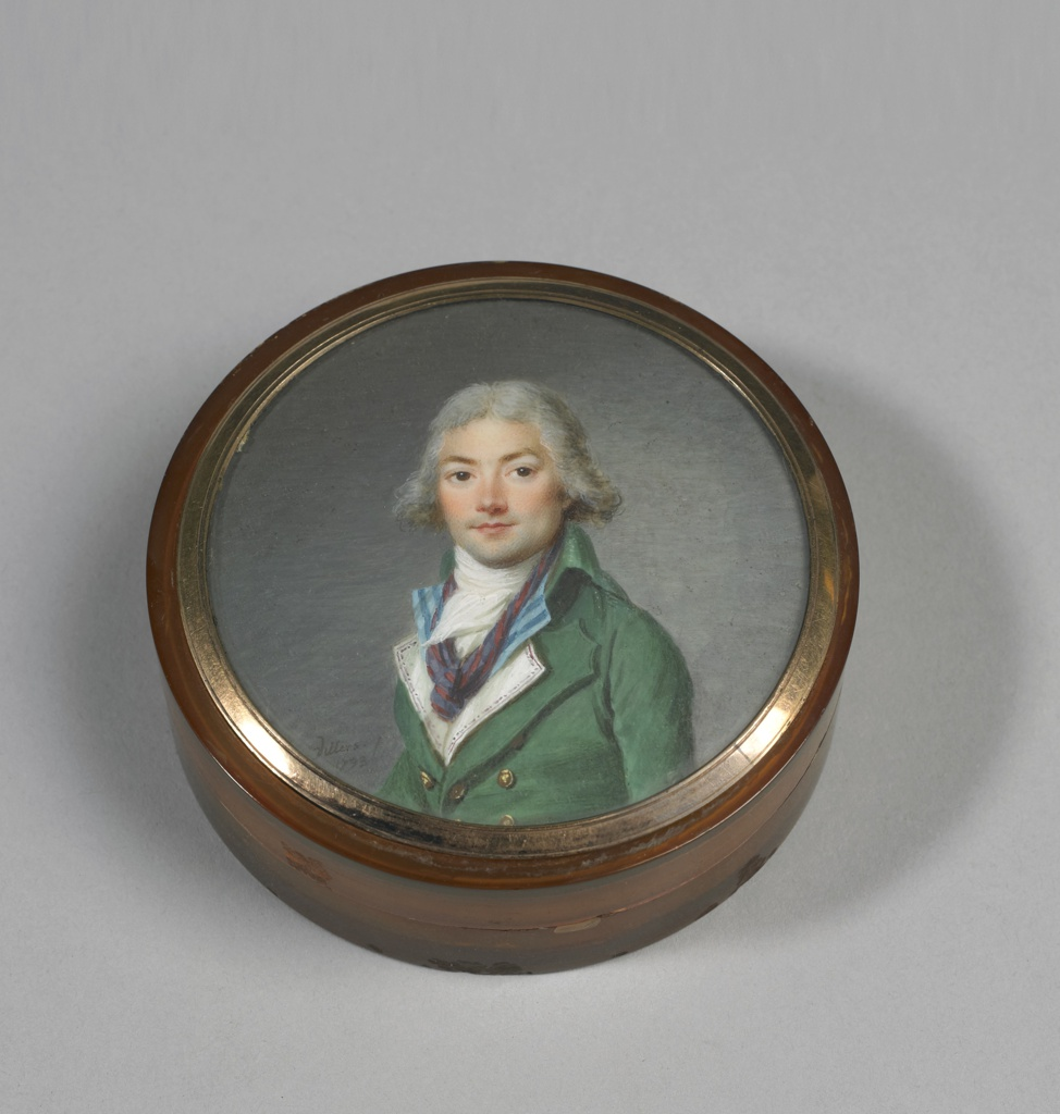 Round box, amber-colored horn, separate cover with portrait of man in green goat, white stock, blue shirt, white waistcoat, purple cravat; gray wig. Gray background, under glass, gold frame.