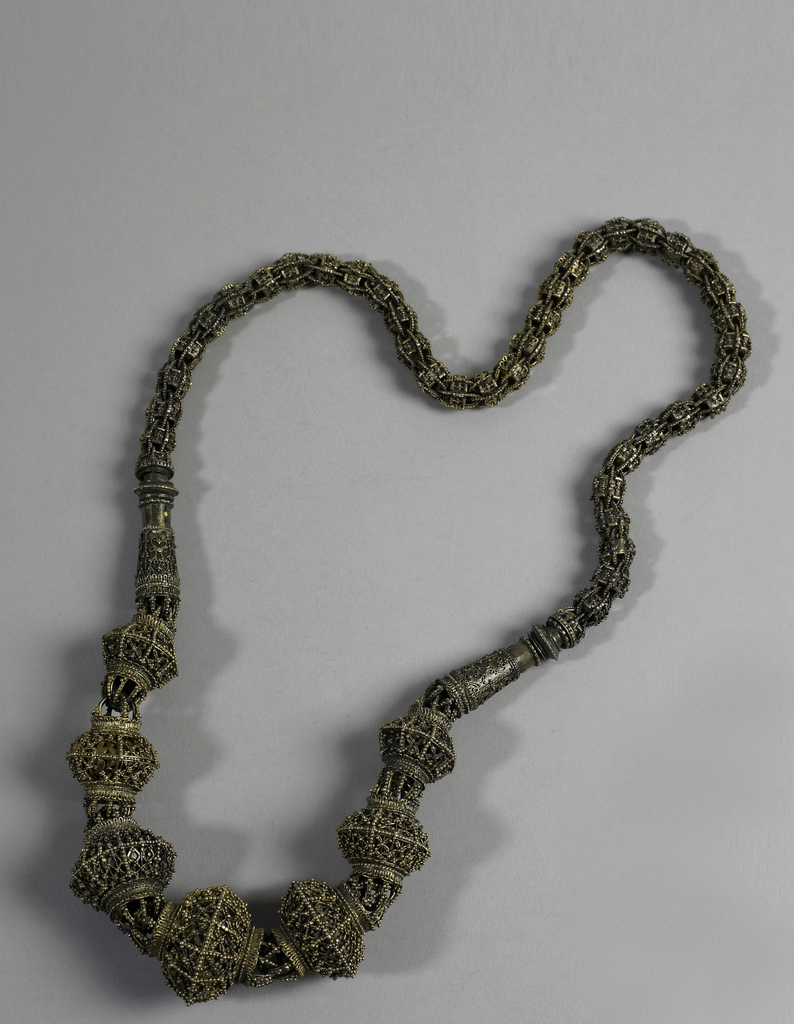 Necklace of gilt silver, made of two distinctly different designed parts. Lower part: seven 12-sided ridged globular units of filigree work and of graduating sizes. Connected by elongated bell-shaped unit to upper part of filigree braided links over circular, small-scaled units.