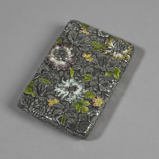A silver card case covered in a floral arrangement.  Flower petals and selected leaves accented with blue, purple and green enamel.