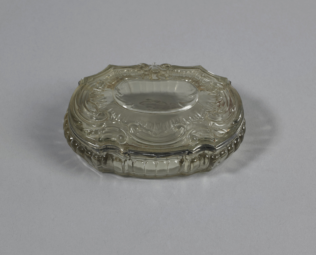 Irregularly octagonal, oblong, hinged cover rock crystal gilt rim. Crystal is carved in central cartouche with plain surface, its frame foliated surmounted by rocaille frame, C-scrolls, base gadrooned.