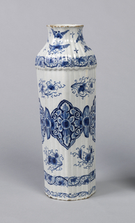 Tall reeded, 8-sided body, bulge at shoulder, tapered neck, slightly flared mouth; painted in underglaze blue on white with large stylized lotus leaf band around center, 3 smaller scroll bands surrounding, and floral/leaf sprays interspersed.