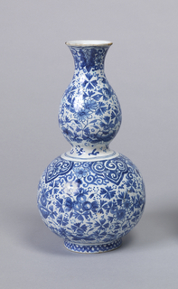 Double-gourd shaped body with flared mouth; underglaze blue on white with dark outlines (trek), overall design of stylized floral pattern, lambrequins at top of lower body section, leaf border top, cross-hatching on short circular foot.