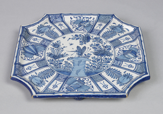"Flat 8-sided tray with raised rim, on three flattened ball feet; painted in underglaze blue on white with center roundel showing dragonfly, rocks, flowers, surrounded by 8 panels painted with ""precious objects"" alternating with flowers; feet painted blue."