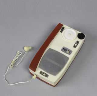 Red and white rectangle, flat metal speaker on top, red stylus along side of body. Dials and controls in white and black.