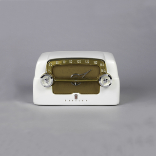 "White rectangular radio with speaker at front. Copper-colored plastic and fabric face with numbers. Control dials in metal. Below, logo and ""CROSLEY""."