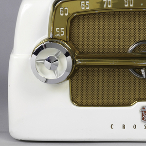 """White rectangular radio with speaker at front. Copper-colored plastic and fabric face with numbers. Control dials in metal. Below, logo and """"CROSLEY""""."""