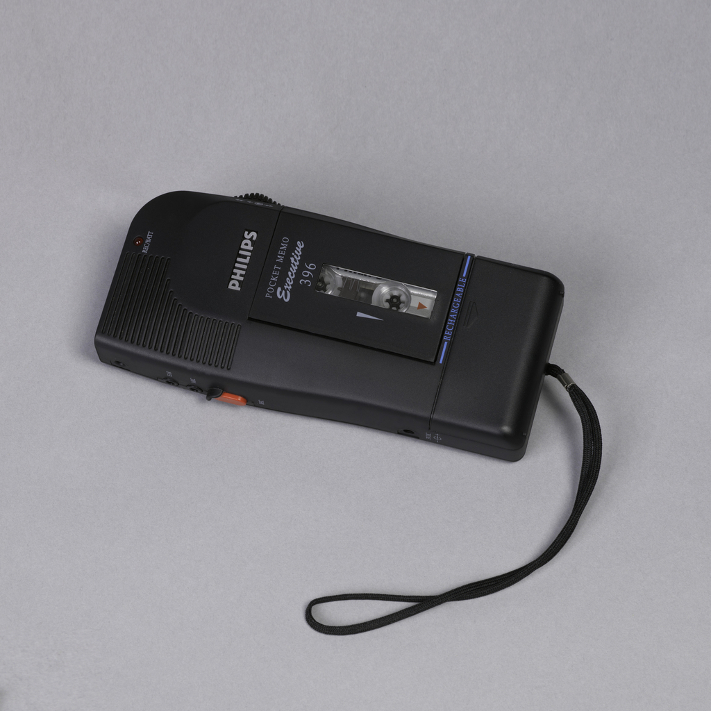 A rectangle Phillips pocket tape cassette with a front loading cassette and speaker. Lanyard attaches to the bottom.