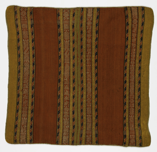 Woolen compound cloth weave. Vertical stripes of geometric designs in red, blue and white alternating with plain cloth ground in yellow and red. Two lengths sewn together. Wool binding around edge.