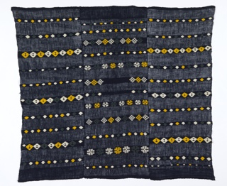 Short huipil formed by three lengths seamed down the long sides. Dark blue loosely woven ground contrasts with narrow tightly-woven horizontal bands of white, yellow and dark green lozenges and rosettes.