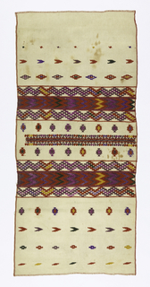 White cotton ground with two broad geometric bands with zigzags on either side in red, yellow, blue and green. Patterned with arrowheads and lozenges in similar colors.