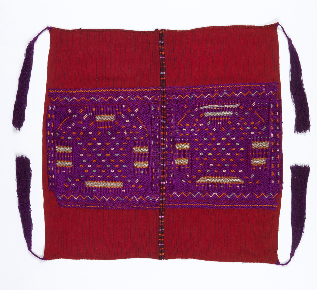 Two widths of hand-woven red cotton with thin blue stripes joined together. Abstract and stylized image of the double-headed eagle in purple, orange, turquoise and white. Long purple tassels at four corners.