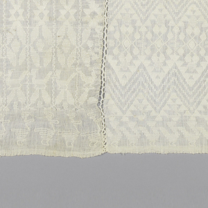Three white-on-white patterned textiles sewn together (each having four selvages). The two outer textiles are patterned with stripes of geometric shapes including a bird. The center is patterned with zigzag bands, one above the other, to form an elongated diamond shape. Head opening is uncut.