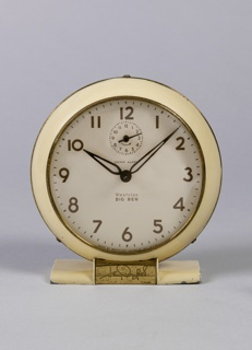 Round, footed alarm clock. White face with brown numbers framed by off-white border, rimmed with brass. Foot with central brass plate showing Henry Dreyfuss signature.