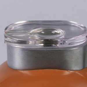 Bell-shaped brown Bakelite body on metal base with horizontal striations; curved metal handle with flat lower section, top section connected to mouth, which is made of metal and topped with glass lid.