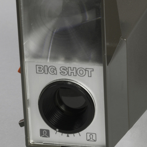 "Dark gray rectangular camera with handle, and flash with words ""BIG SHOT""."