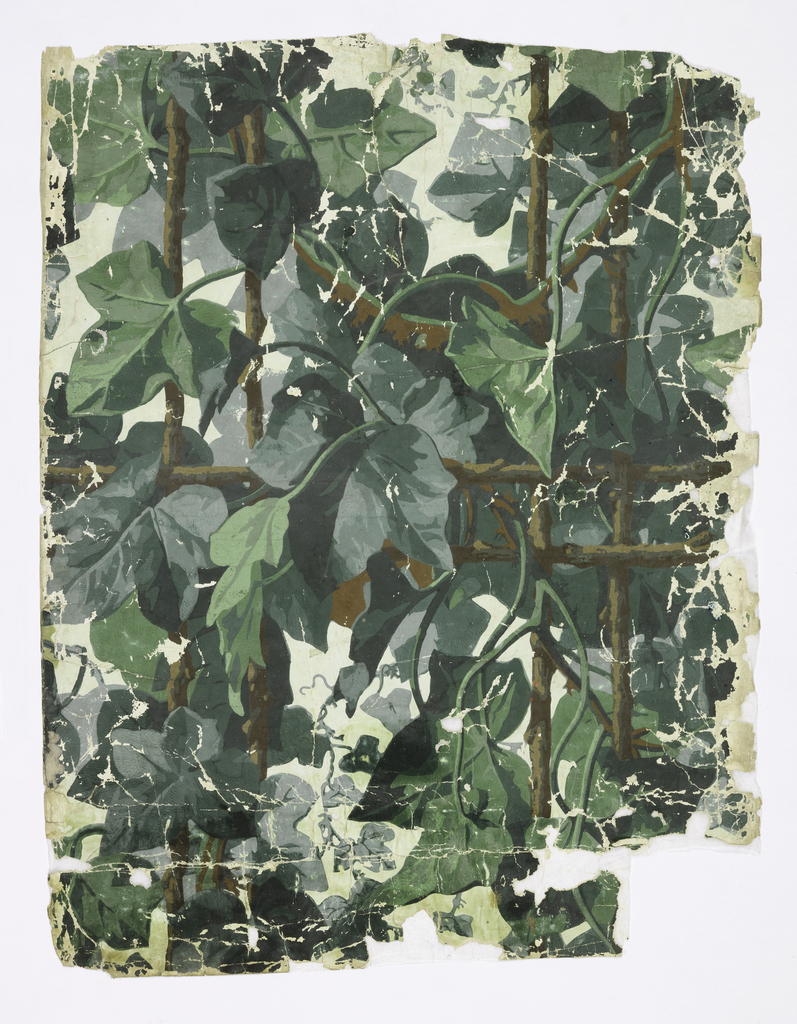 On white ground trellis work of thick brown branches with oversized ivy leaves entwined.