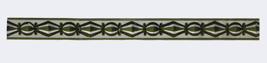 """The design of this narrow border is edged by flocked stripes and consists of a modelled """"chain"""" of wrapped candy-like shapes (spheres alternating with lozenges). Flocking of olive, light green, dark green and black over a gray ground with white shades of gray highlighting.  H# 300"""
